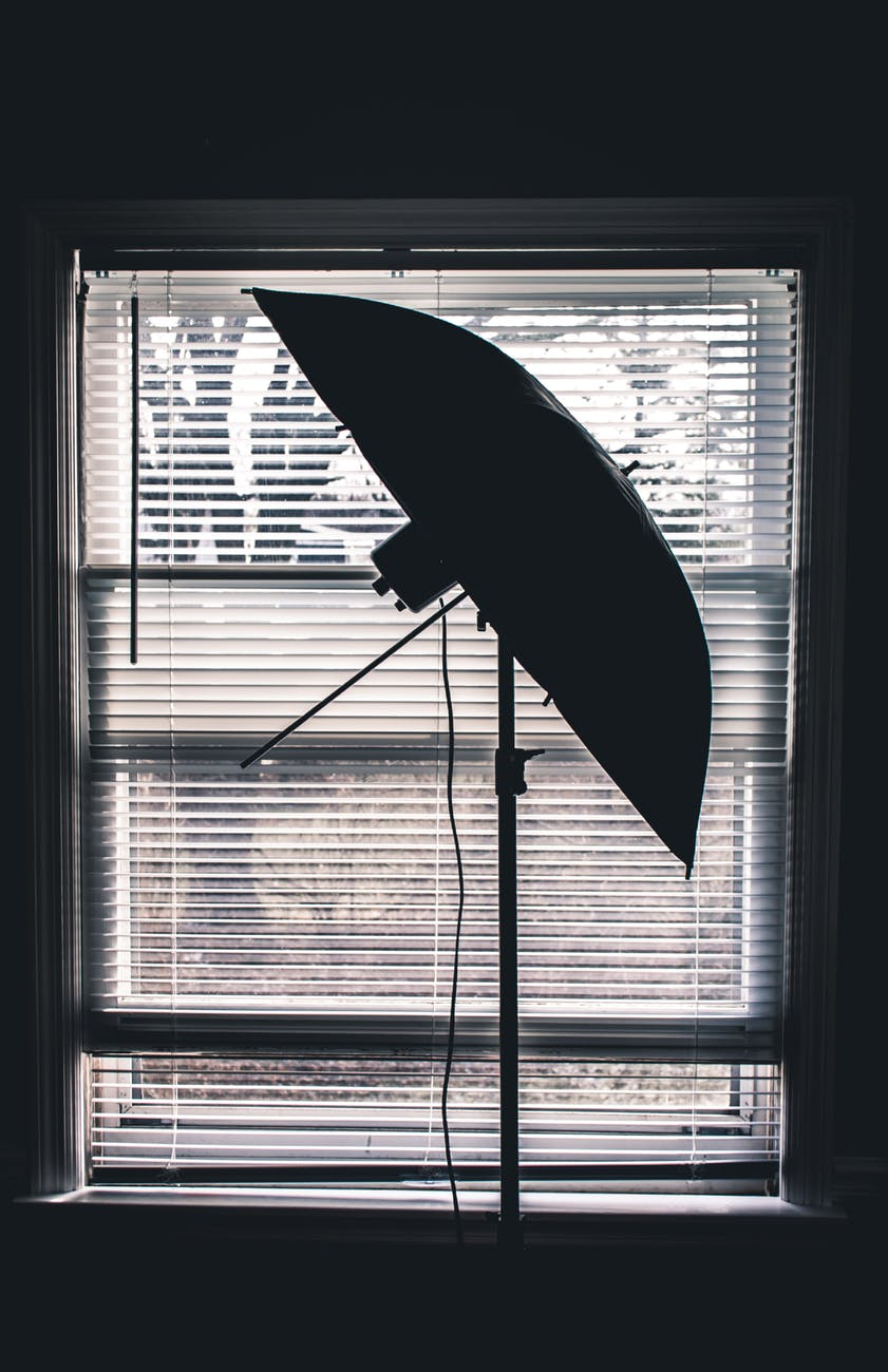 silhouette photo of studio umbrella near white window blinds inside room